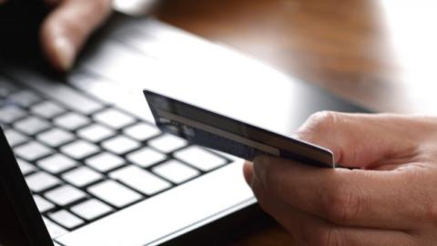 Person shopping online with credit card.